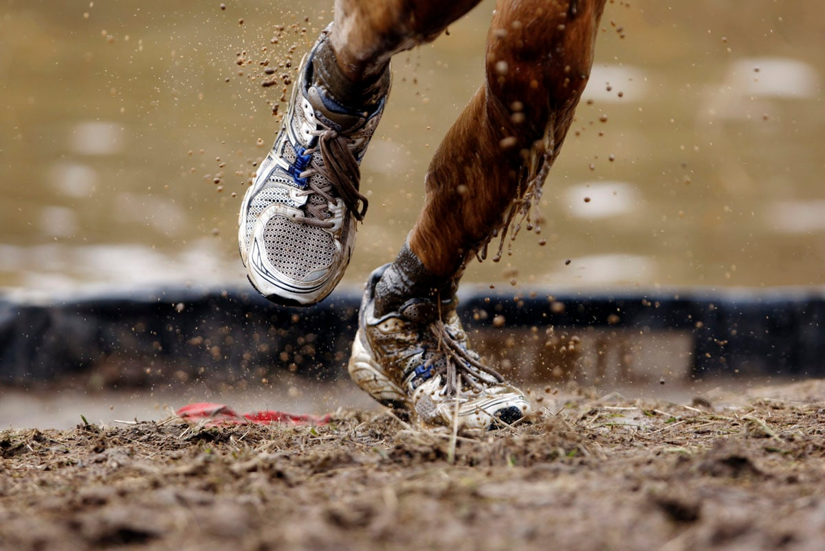 Mud flies off a competitor's shoes as he runs out of an obstacle during the Tough Mudder at Mt. Snow in West Dover