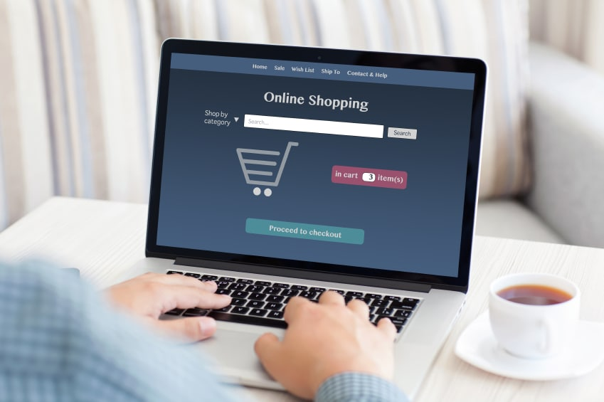 man sitting at a computer and makes online shopping